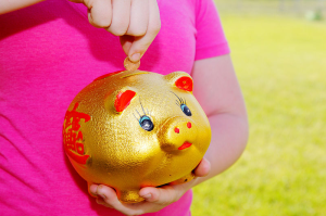 Girl Purring Money Into Piggy Bank