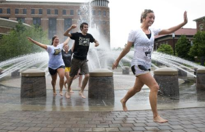 students running through fountain