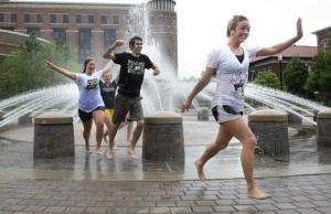 students running through fountain