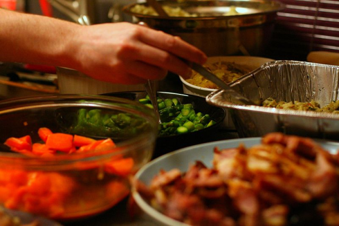 Person filling plate from buffet